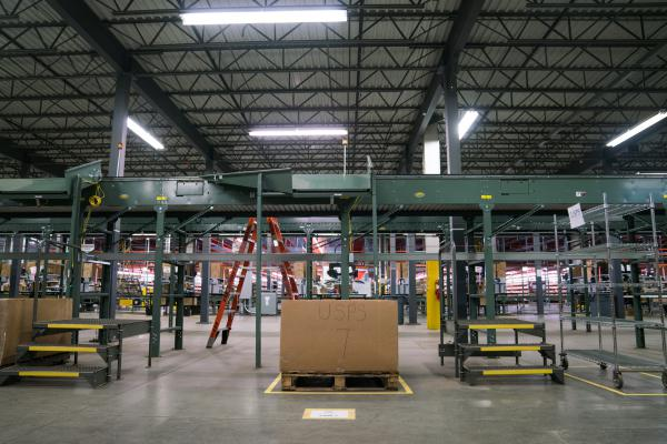 "A conveyor belt, one of two types of automation at the Radial warehouse, fetches boxes from the packing station and sorts them by shipping type, depositing them directly into bins with labels like ""USPS""."