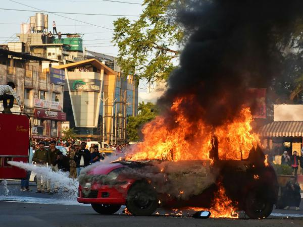 Firefighters work on a car set ablaze during a protest against the screening of the Bollywood film <em>Padmaavat</em> at Jyoti Chowk in Bhopal, Madhya Pradesh, on Thursday.