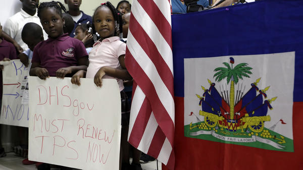 Children hold signs at a November news conference in Miami in support of renewing temporary protected status for immigrants from Central America and Haiti.