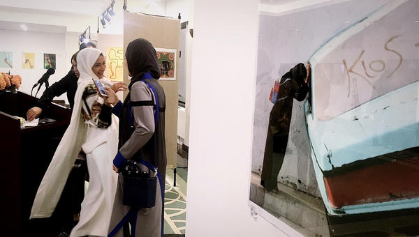 Artists chat at the exhibition opening. A photograph by Dar Al-Hekma graduate Lina Jamjoon of a woman leaning against a car sculpture at a Jeddah landmark hangs on a wall nearby.