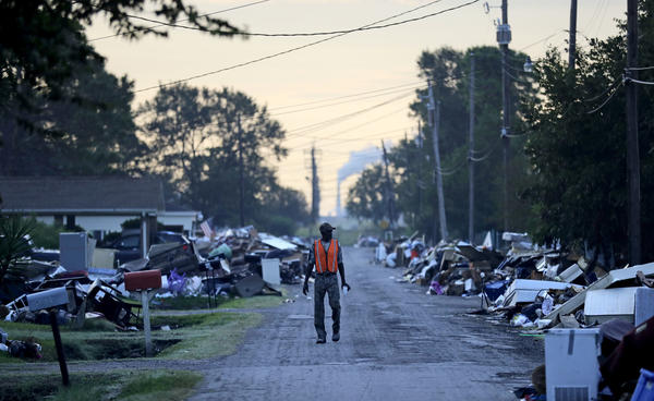 A man walks past debris from Hurricane Harvey in September in Port Arthur, Texas.