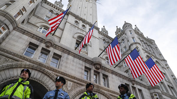 Police stand guard outside the Trump International Hotel, blocks from the White House, last year. The hotel has become a centerpiece of lawsuits claiming the president is profiting from the office.
