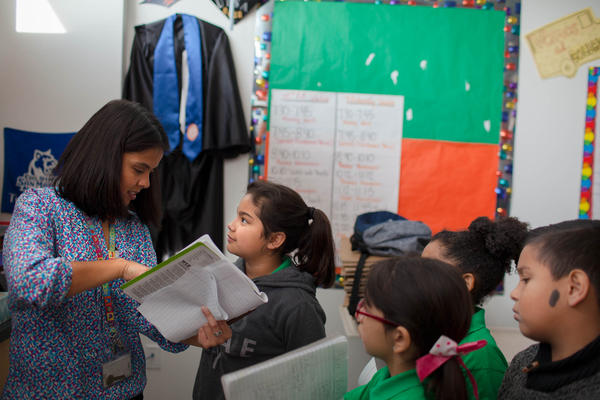 Rocha checks her student's work during her third-grade science class.