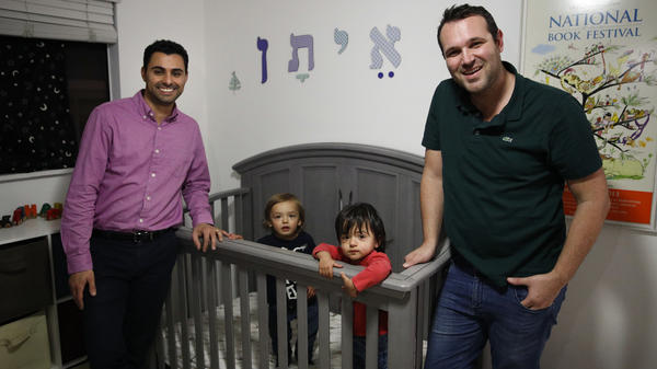 Elad Dvash-Banks (left) and his husband, Andrew, pose for photos with their twin sons, Ethan (right) and Aiden, in their Los Angeles apartment on Tuesday. Ethan is a plaintiff in a federal lawsuit against the State Department that seeks the same rights as his brother, who is a U.S. citizen.