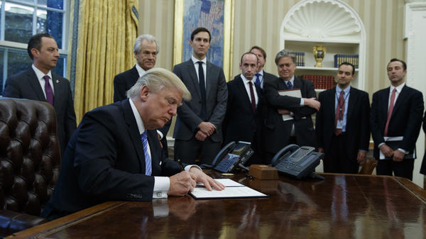 President Trump signs an executive order implementing a federal government hiring freeze, on Jan. 23, 2017, in the Oval Office of the White House.