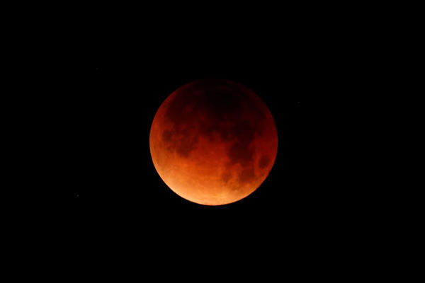 A lunar eclipse is shown over the ocean in Oceanside, Calif.