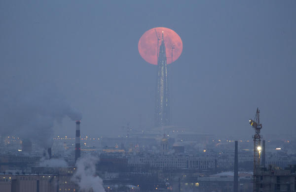 The moon is seen behind the business tower Lakhta Centre, which is under construction in St. Petersburg, Russia.