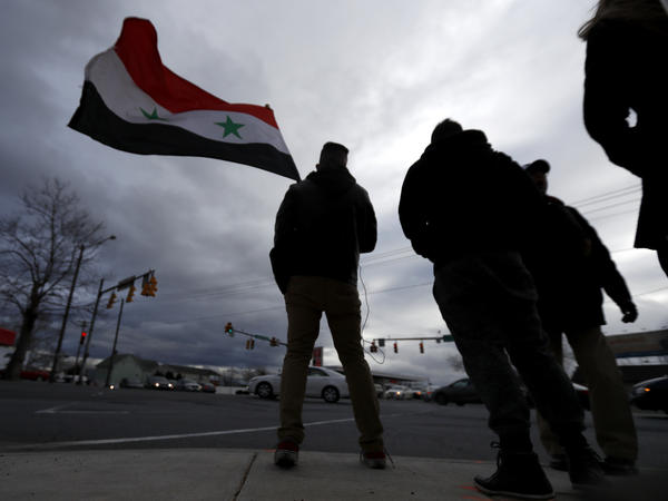 A man waves a Syrian flag during a rally last year in Allentown, Pa., which has one of the largest Syrian populations in the U.S.