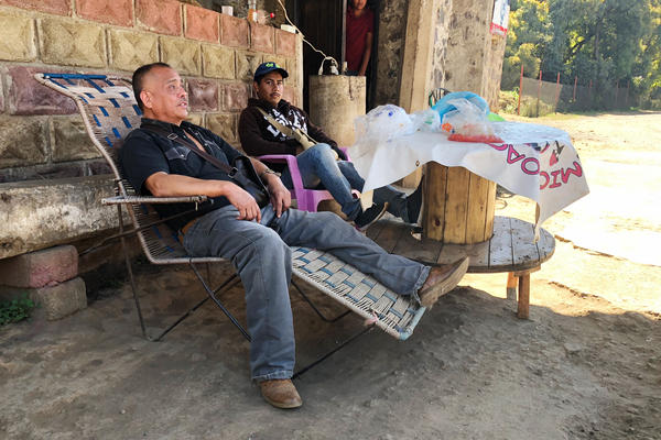 Rafael Cortez Pérez guards a road leading into Tancitaro with his nephew. He is one of 16 civilian crews that watch the roads and report any suspicious visitors or activity to the Tancitaro police. Cortez, who doesn't get paid, says it's a lot of time to volunteer, but worth it for the town's peace and tranquility.