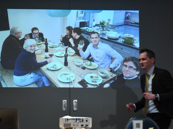 A screen shows ousted Catalan separatist leader Carles Puigdemont (right) eating a meal with members of the Belgian Flemish nationalist party New Flemish Alliance on Tuesday in Leuven. Puigdemont has befriended nationalists seeking independence for the region of Flanders since he fled to Belgium in October.