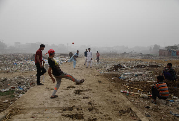 Youths play cricket in a trash field near where Zainab's body was found on Jan. 9.