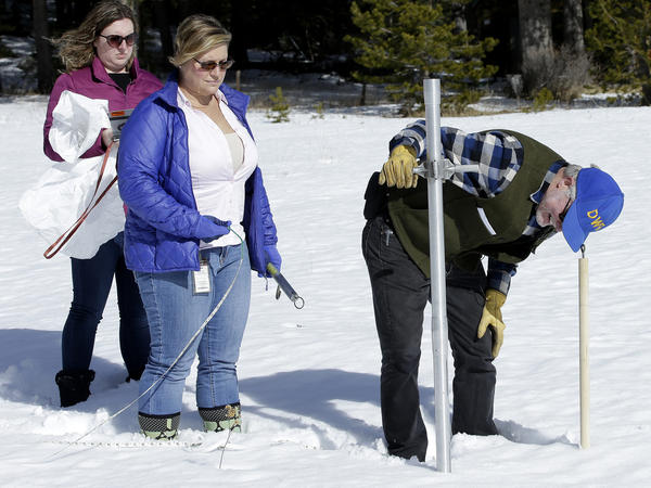 Frank Gehrke of California's Department of Water Resources checks the snowpack depth with Courtney Obergfell and Michelle Mead of the National Weather Service.