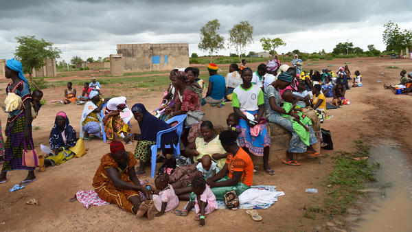 Women wait by a maternal health care clinic in Pabre, Burkina Faso, for a free cervical cancer screening.