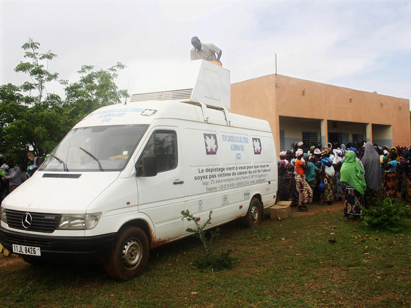 Women wait outside a maternal health facility in Pabre, Burkina Faso, to be screened for cervical cancer in this minibus. The vehicle is outfitted with a metal exam table and a nitrous oxide gas tank.