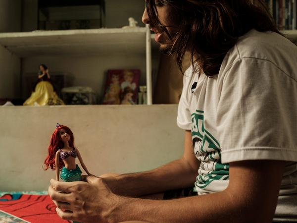 """Merman"" Davi de Oliveira Moreira holds a doll of Ariel from Disney's <em>The Little Mermaid</em> at his home in Rio de Janeiro, Brazil, on May 3. The 22-year-old Brazilian is part of a growing mermaid craze in Brazil."