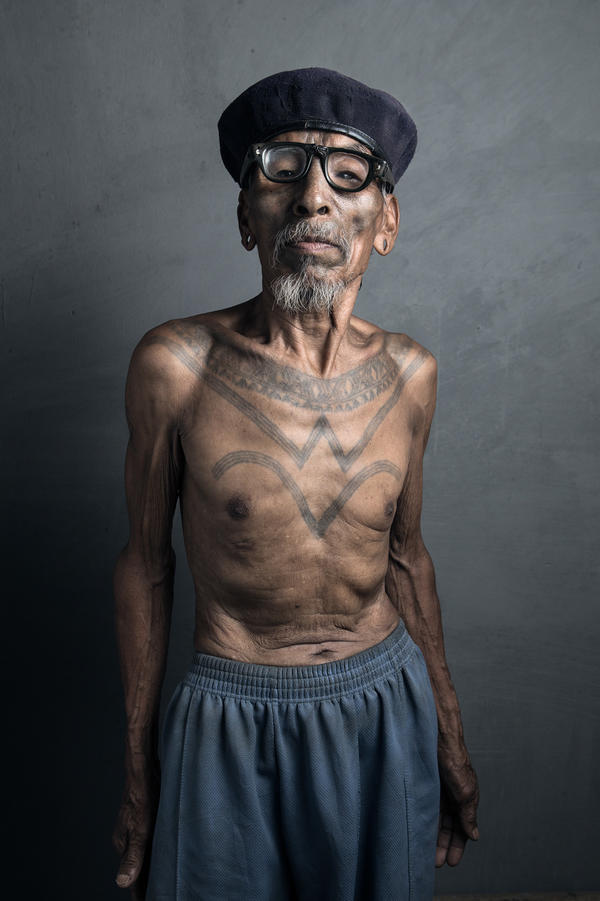 Pennga, 82, displays his chest tattoo, etched onto young teenagers as a rite of passage into manhood.
