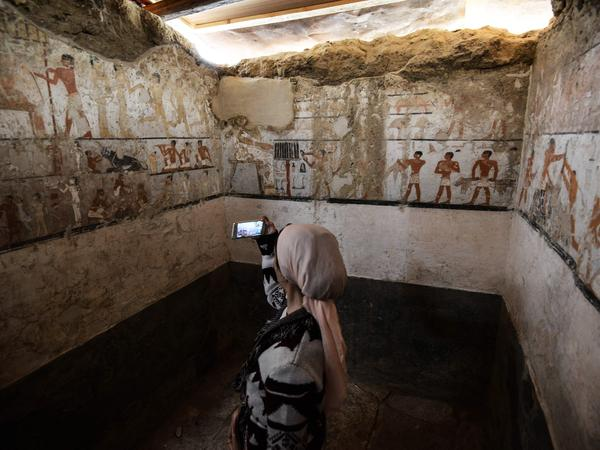 A woman takes a photo inside the tomb of an Old Kingdom priestess that was unveiled on Saturday after being discovered during excavation work in Giza's western cemetery by a team of Egyptian archaeologists.