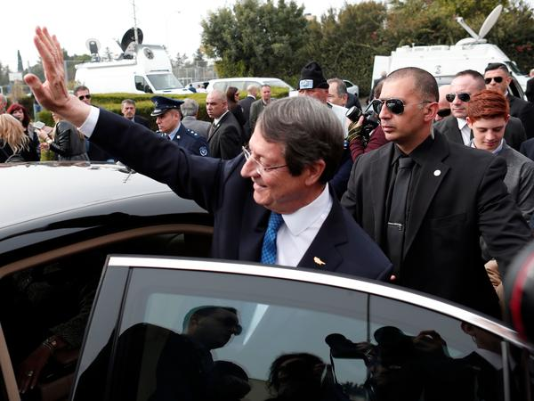 President of Cyprus Nicos Anastasiades waves to his supporters after casting his ballot at a polling station in the coastal city of Limassol on Sunday during the second round of the Cyprus presidential elections.