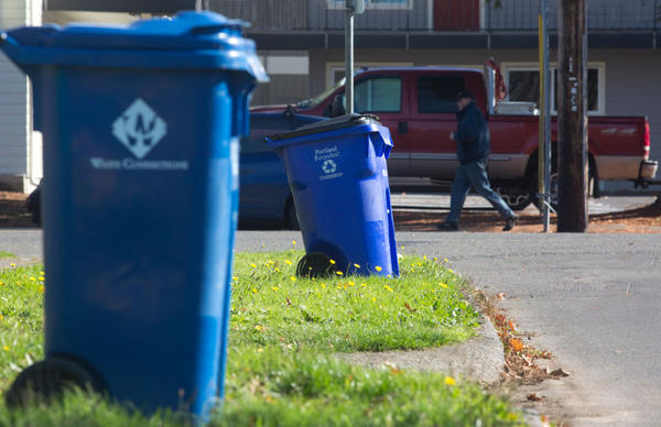 Blue recycling bins are seen on a residential street, Oct. 30, 2017 in Portland, Oregon. China is sharply restricting imports on recycled materials, and the impact will be felt across the Pacific Northwest. (Natalie Behring/Getty Images)
