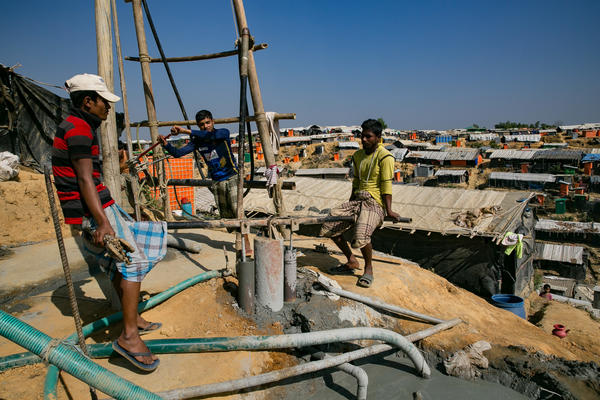 "Two men operate what's called a ""donkey pump"" as they drill a new water well in the Balukhali refugee camp. Aid groups are providing funds and materials to dig deeper wells that are less likely to get contaminated during seasonal flooding."