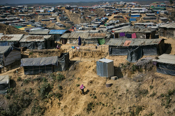 A woman carries water up a steep hill in the Balukhali Rohingya refugee camp in Bangladesh. Aid workers say these slopes may collapse in the coming monsoon rains.