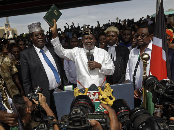 """Opposition leader Raila Odinga holds up a bible, center, accompanied by lawyers Miguna Miguna, center-left, Tom """"T.J."""" Kajwang, center-right, and politician James Orengo, right, after taking an unauthorized oath of office in Uhuru Park in downtown Nairobi, Kenya."""