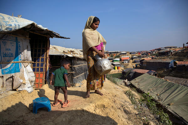 Sanura Begum stands with her son, Abdur Sobor, outside her plastic and bamboo shelter in the Kutupalong refugee camp in Bangladesh. One of the things she misses most about Myanmar is her family's wooden house.
