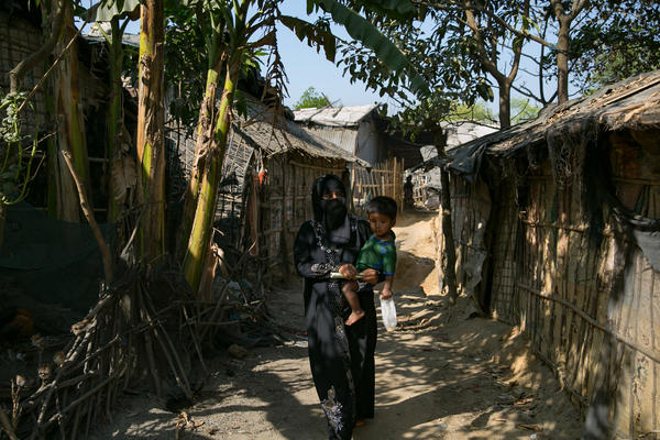 Sanura Begum walks with her son, Abdur Sobor, through the Kutupalong camp in Bangladesh. This refugee camp is now the largest in the world, with 547,000 Rohingya living there.