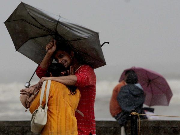 A couple walks in the rain in Mumbai in 2007.