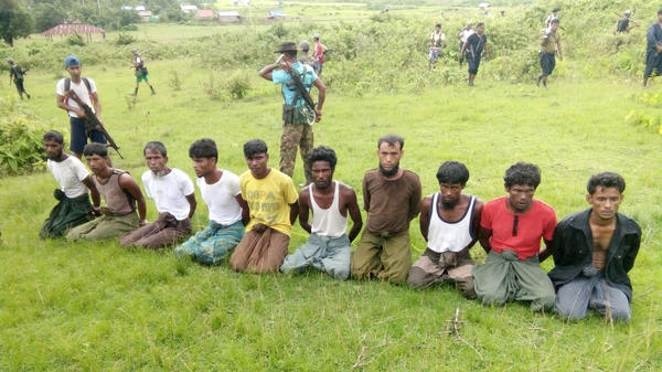 Ten Rohingya Muslim men kneel with their hands bound as members of the Myanmar security forces stand guard in Inn Din village on Sept. 2, 2017. The photo has been published as part of an extensive Reuters investigation into the massacre of the 10 men, who were fishermen, shop owners, high school students and an Islamic teacher.