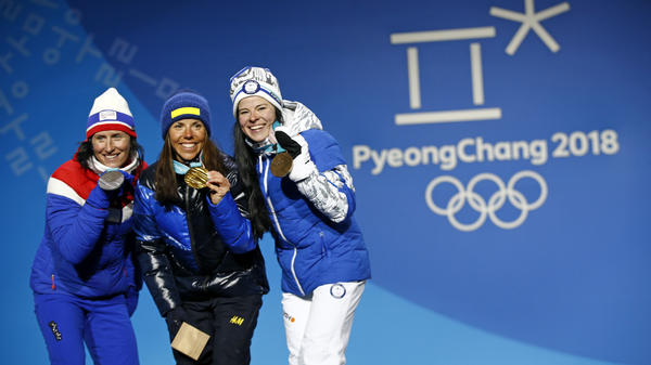 The first medals of the 2018 Winter Olympics, in the women's cross-country 15-kilometer skiathlon, were won by (from left) Norway's Marit Bjoergen, silver; Sweden's Charlotte Kalla, gold; and Finland's Krista Parmakoski, bronze.