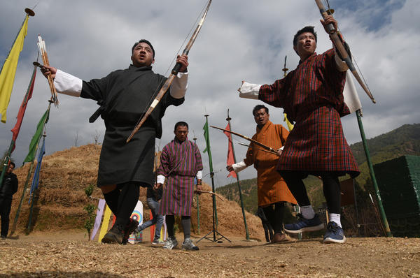 Archers indulge in a raucous competition, cheering teammates and jeering opponents. Here archers celebrate with a ritual dance after a teammate hit the narrow target.