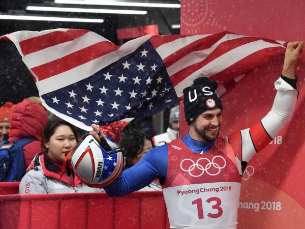 Chris Mazdzer waves the American flag after earning his silver medal in men's singles luge Sunday in Pyeongchang.