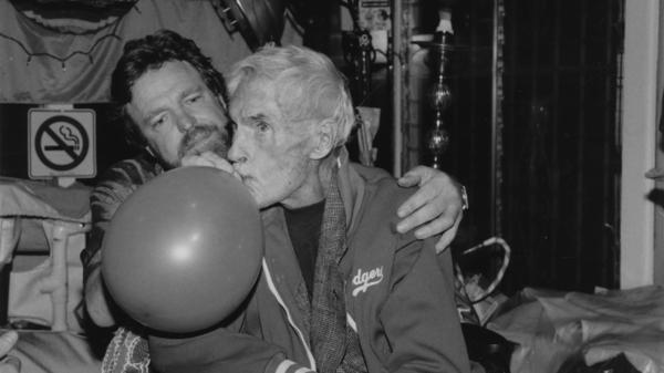 John Perry Barlow administers a balloon filled with nitrous for pain relief to Timothy Leary in 1996.