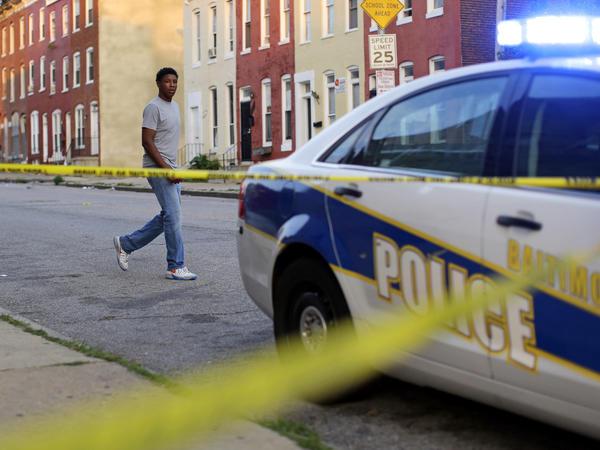 A man walks past a Baltimore police patrol car.