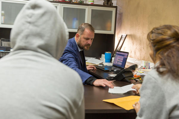Attorney Christopher Taylor speaks with clients in his office in Norcross, Ga., a suburb of Atlanta. Arrests of immigrants with no criminal record more than tripled in the region last year.