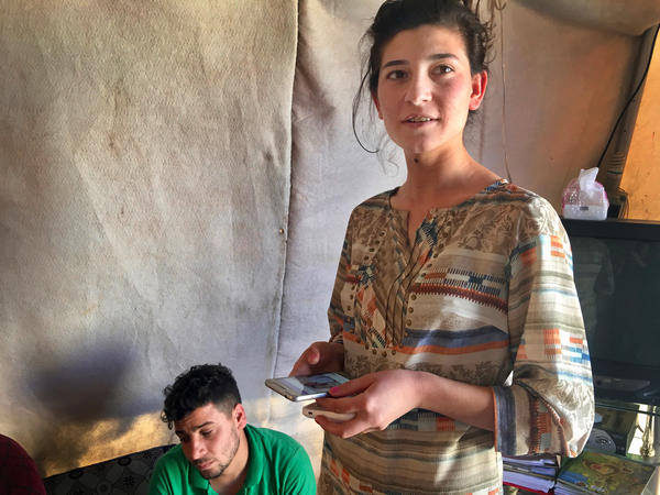 """Hadiya Haskan and her husband Amin Shani Bagi in their tent in a camp for displaced Yazidis in the Kurdistan region of Iraq. Haskan is 19 and in 11th grade. She dreamed of going to college but says she had to get married because her family needed the money. """"It's alright though because I love him,"""" she says."""