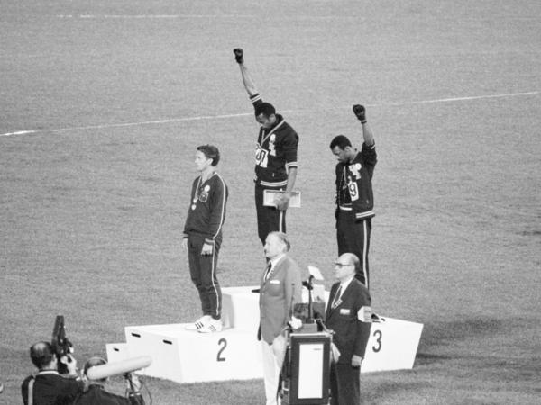 Tommie Smith and John Carlos, gold and bronze medalists in the 200-meter run at the 1968 Olympic Games, raise their fists to protest the inequity and discrimination that black people in the U.S. face.