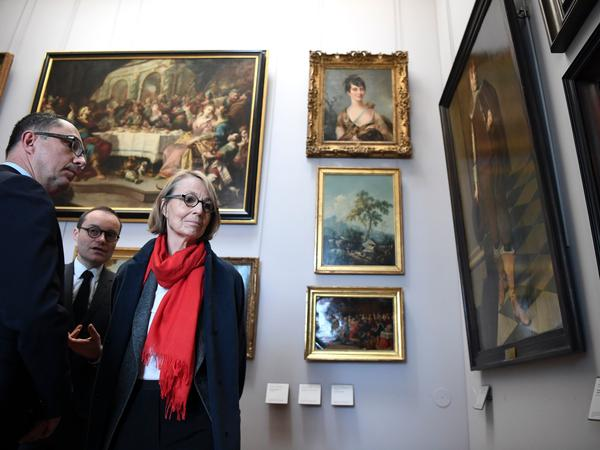 French Culture Minister Francoise Nyssen, wearing a red scarf, visits two rooms of the Louvre filled with 31 paintings recovered after World War II. She conducted the visit Monday with the museum's president, Jean-Luc Martinez.