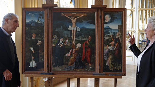 Christopher Bromberg and Henrietta Schubert, grandchildren of Henry and Hertha Bromberg, view Flemish painter Joachim Patinir's <em>Triptych of the Crucifixion</em>, which was returned to them Monday by the French state.