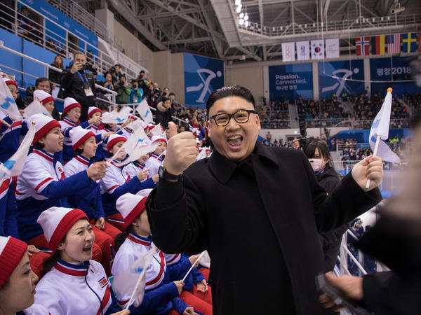 A man impersonating Kim Jong Un throws out a thumbs up in front of the North Korean cheerleaders attending an Olympic women's ice hockey game Wednesday.