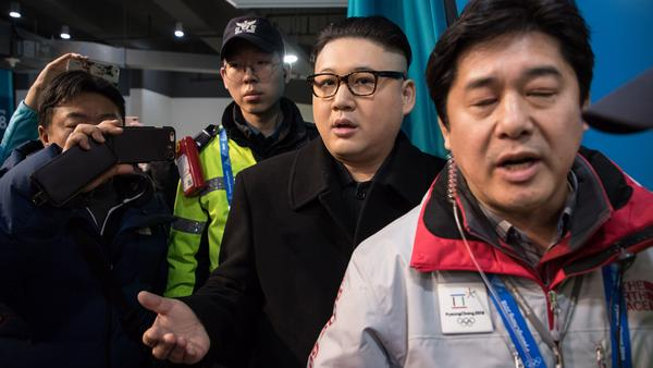 The faux Kim leaves the stands escorted by South Korean police and venue staff, now looking rather more nonplussed than his star turn in front of the cheerleaders.
