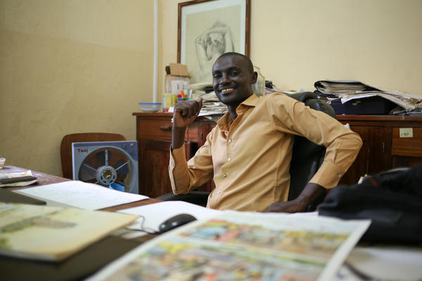 """Didier Kassai uses comics to """"transmit a message."""" His father opposed to a career in art until Kassai began earning money for his drawings. Here he sits in his office in Bangui, capital of the Central African Republic."""