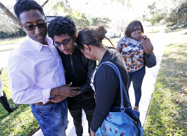 Family members embrace after a student walked out of the high school.