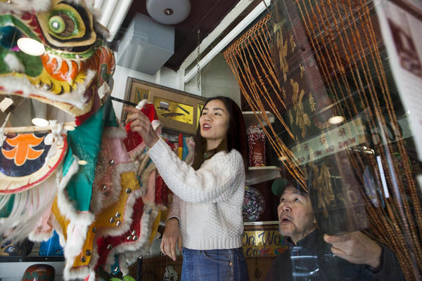Gary Lum assists his daughter, Mei Lum, with decorating the storefront window at Wing on Wo & Co. for the Lunar New Year in the Chinatown neighborhood of New York City. The family imported the unique handmade lion-head dance costume from Hong Kong nearly 50 years ago.