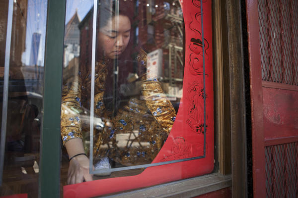 Artist Emily Mock installs a paper-cut display at Wing on Wo & Co.'s storefront window.