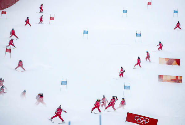 Slippers prepare the ski course before the first run of the women's giant slalom.