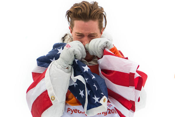 U.S. snowboarder Shaun White wraps himself in the U.S. flag after winning gold in the men's halfpipe. He was later criticized for dragging a flag on the ground.