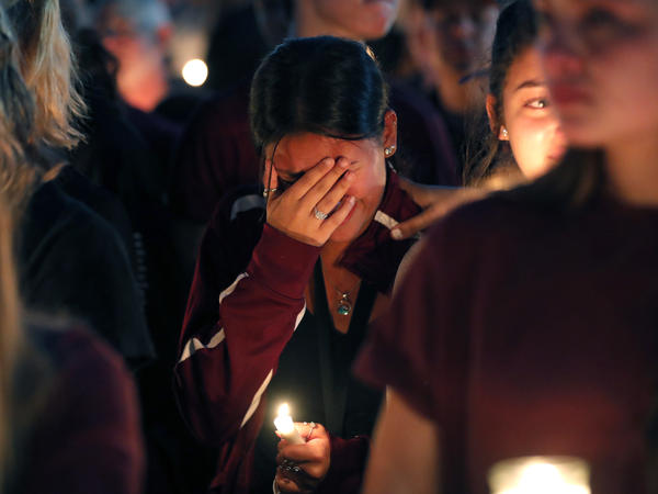 A woman cries during a candlelight vigil for the victims of Wednesday's shooting at Marjory Stoneman Douglas High School, in Parkland, Fla.