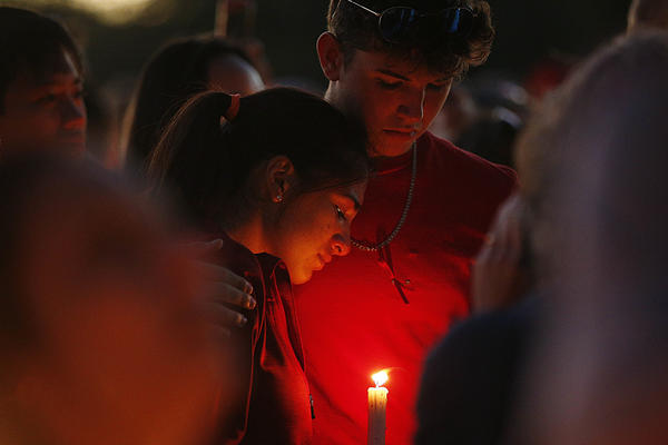 Students mourn at Pine Trails Park. They are among thousands attending the gathering Thursday night in Parkland, Fla.